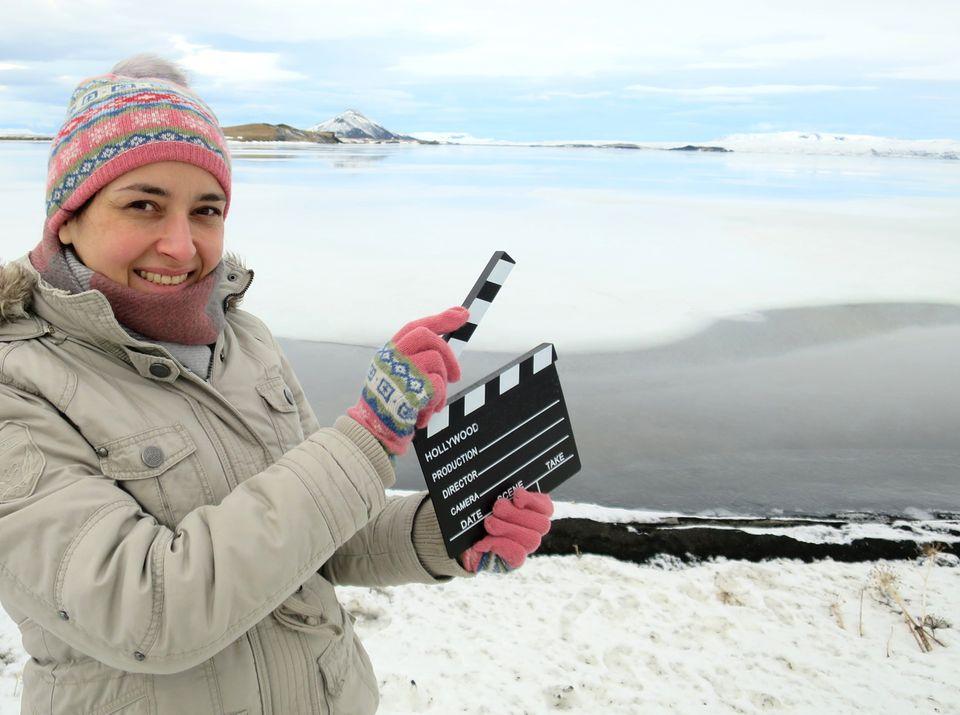 Andrea David hält eine Filmklappe amMývatn auf Islandin die Höhe. Die Hamburgerin bereist Filmkulissen in der ganzen Welt und berichtet auf ihrem Online-Blog darüber.