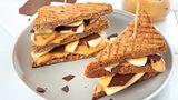 Chocolover's Erdnussbutter- Banana-Sandwich      Zutaten:  Für die Erdnussbutter: 150 g geröstete, ungesalzene Erdnusskerne, 20 g Vollrohrzucker, 1 TL Kokosöl, 1 Msp. Vanilleextrakt, 1 Prise feines Meersalz  Für die Schokotäfelchen: 75 g Zartbitterschokolade (mind. 70 %)  Für das Sandwich: 1 kleine Banane 8 Scheiben Vollkornsandwichbrot  Außerdem: Back- oder Pergamentpapier      Zubereitung:  Die Erdnüsse in eine Küchenmaschine oder einen Standmixer geben und 2–3 Minuten mixen bis eine glatte, cremige Masse entstanden ist. Den Vollrohrzucker, das Kokosöl, den Vanilleextrakt und das Salz zufügen und nochmals etwa 1 Minute mixen, bis sich alle Komponenten gut verbunden haben. Die Schokolade grob hacken und über einem heißen Wasserbad vorsichtig schmelzen. Ein glattes Stück Back- oder Pergamentpapier auf einem großen Brett auslegen, die Schokolade darauf gießen und mit einem Löffel oder einer Winkelpalette glatt und dünn verstreichen. Das Brett für etwa 15 Minuten in den Kühlschrank stellen. Die Schokolade mit einem Pizzaschneider oder scharfen Messer in Rechtecke schneiden. Falls noch einige Stellen der Schokolade zu weich sind, nochmals in den Kühlschrank stellen und dann den Rest in Rechtecke schneiden. Die Banane schälen und in dünne Scheiben schneiden. Die Brotscheiben rösten und die Hälfte der Brotscheiben mit Erdnussbutter bestreichen. Die Bananenscheiben und Schokotäfelchen auf den Brotscheiben verteilen, mit den übrigen Brotscheiben abdecken, diagonal halbieren und servieren.      Mehr Rezepte finden Sie in in: Sporternährung für jeden Tag, 240 Seiten, 29,99 Euro