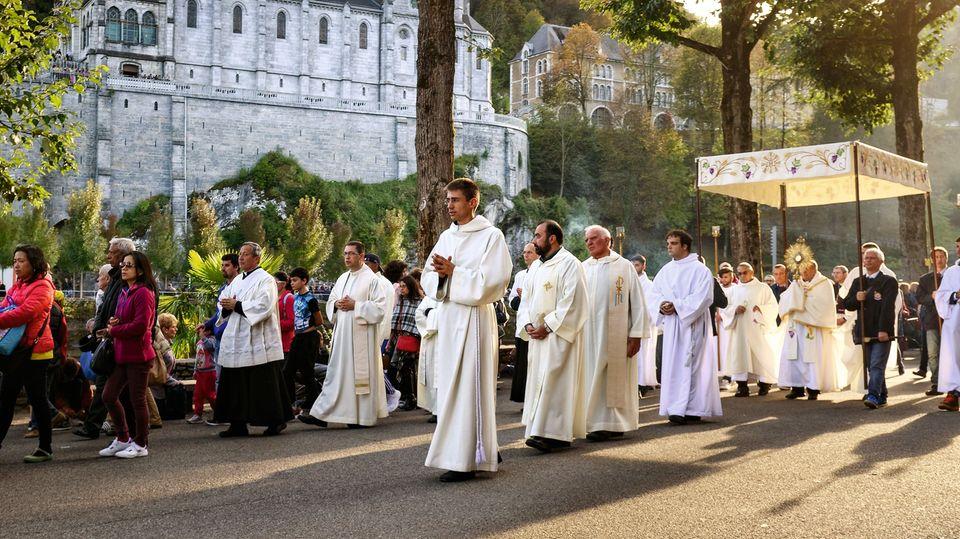 Durch den Wallfahrtsort Lourdes zieht eine Prozession von Marienverehrern