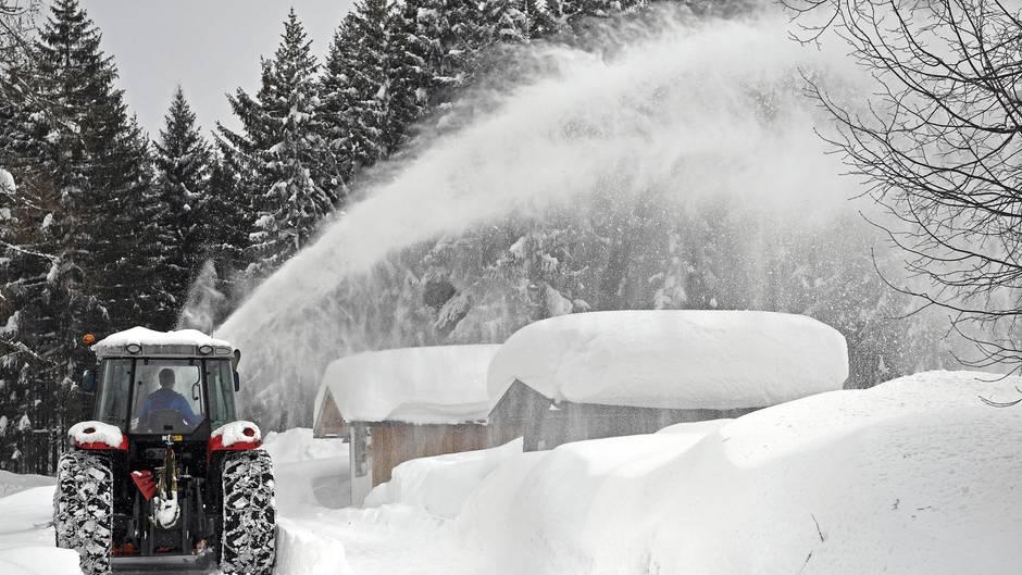 Ein Schneepflug räumt Schnee von einer Straße im österreichischen Ramsau Am Dachstein
