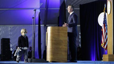 Gavon Newsom hinter dem Rednerpult, sein Sohn steht mit Schnuller und Kuscheldecke davor
