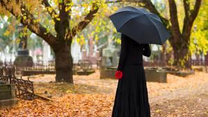 Eine mysteriöse Frau, steht einsam abseits bei einer Beerdigung