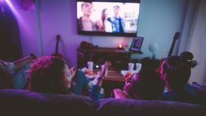 Menschen, die auf einem Sofa sitzen und einen Film sehen