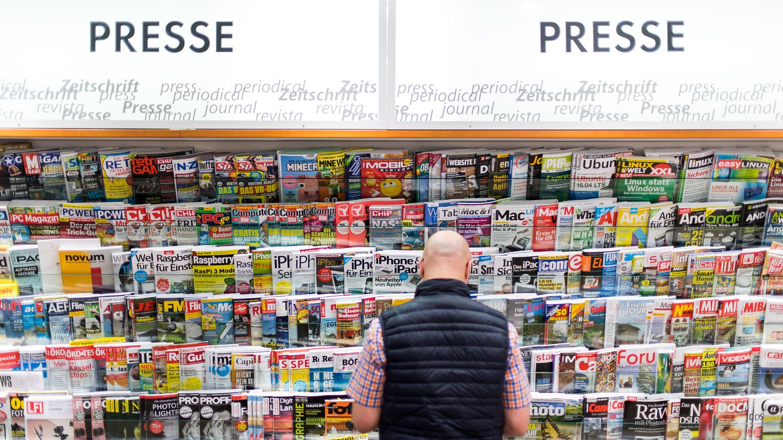 Ein Mann steht vor einem Zeitschriftenregal
