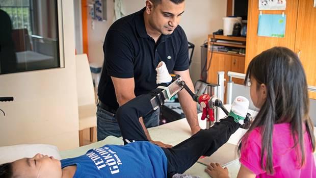 Göksel Kirac hat ein Tretrad für seinen Sohn gebaut, damit die Gelenke nicht steif werden. Senay, Gökhans Schwester, hilft mit, seine Beine zu bewegen.