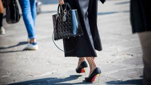 Frau in Culotte und High-Heels läuft über die Straße