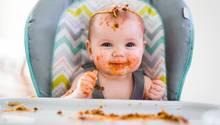 Ein tomatensoßenverschmiertes Baby lächelt glücklich in die Kamera