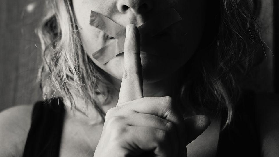 Frau hält sich Finger vor den Mund