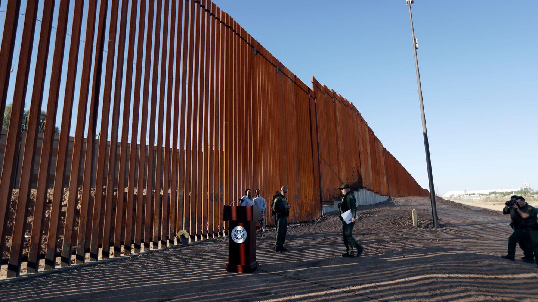 USA, Calexico: Grenzschutzbeamte stehenneben einem neuen Abschnitt der Grenzmauer zwischen den USAund Mexiko