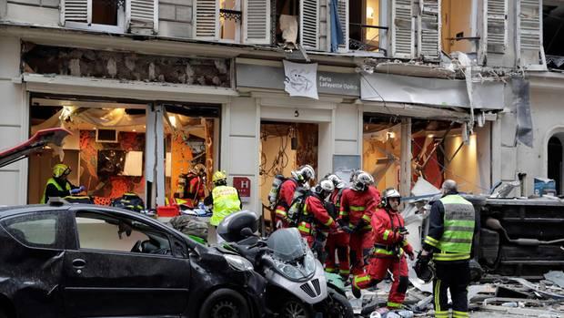 Einsatzkräfte in Paris tragen eine verletzte Person aus einem zerstörten Gebäude