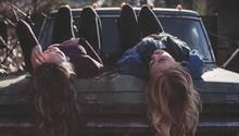 Zwei Freundinnen liegen auf einer Motorhaube