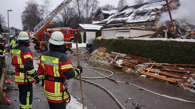 Feuerwehrleute stehen bei einem zerstörten Reihenhaus