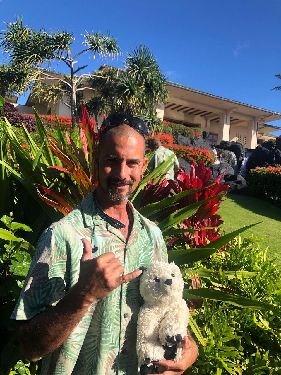 Der Landschaftgärtner des Hotels grüßt in die Kamera – mit dem Teddy auf dem Arm