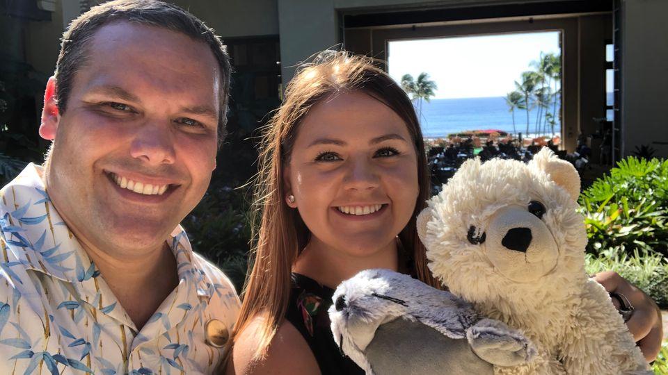 Die beiden Hotelangestellten lächeln mit Teddy und Robbe in die Kamera