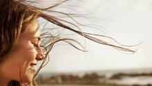Frau im Wind mit geschlossenen Augen