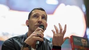 Ex-Handballer Stefan Kretzschmar sitzt auf einer Bühne und spricht in ein Mikro in seiner rechten Hand