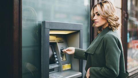 Eine Frau hebt am Geldautomaten Geld ab