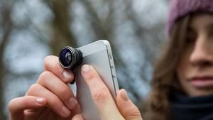 Eine junge Frau fotografiert mit ihrem Smartphone