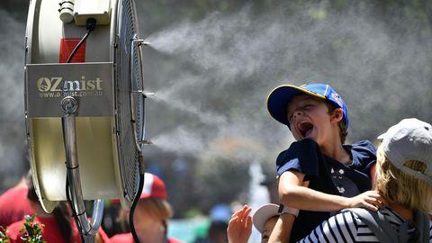 Ein Kind hält sein Gesicht in einen Ventilator, der auch Wassertröpchen versprüht