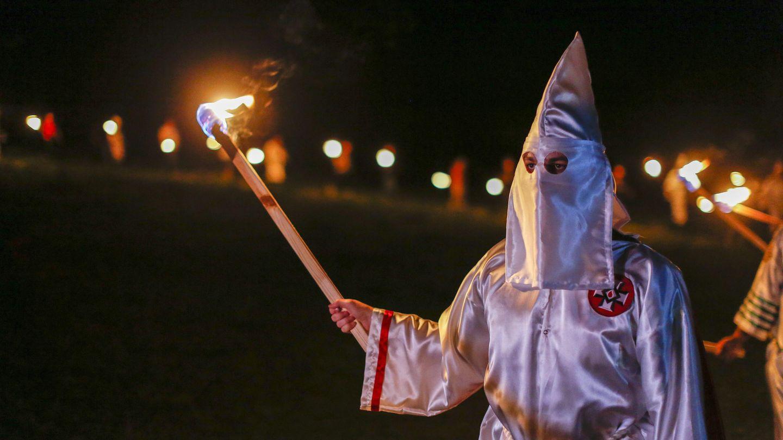 Ein Mitglied des Ku Klux Klan hält eine Fackel in der rechten Hand, während er das weiße Gewand und Mütze des Klans trägt