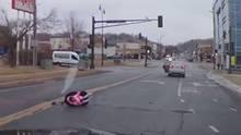 Kind fällt mit Kindersitz aus fahrendem Auto