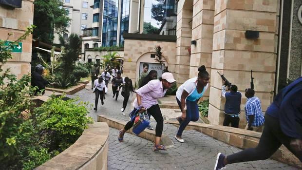 Über einen Weg am Hotel vorbei fliehen Menschen, während Sicherheitskräfte die Angreifer im Hotel ins Visier nehmen