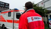 Ein Rettungssanitäter steht vor einem Rettungswagen