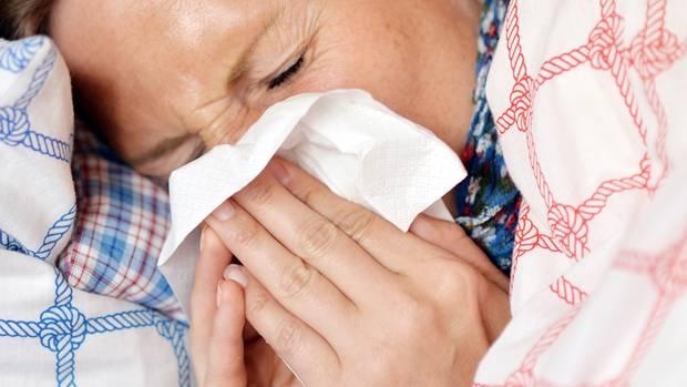 Eine Frau liegt mit hochgezogener Decke im Bett und putzt sich mit einem Papiertaschentuch die Nase