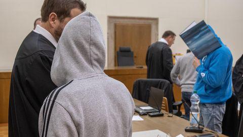 Die Angeklagten stehen im Gerichtssaal und verbergen sich unter den Kapuzen ihrer Pullover und hinter einem Aktenordner