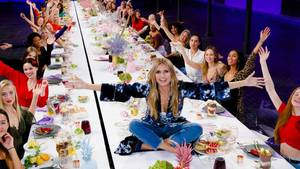 Heidi Klum sitzt auf einer langen Tafel und präsentiert die Kandidatinnen von GNTM 2019