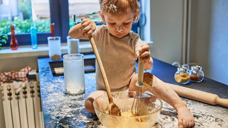 Ein kleiner Junge schmiert mit Mehl und Kuchenteig herum