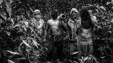 Eine Gruppe von Shuar-Freiwilligen der Dorfgemeinschaft Shariant posiert im Dschungel. Die Männer mit den selbst gefertigten Waffen sehen sich als Verteidiger Amazoniens.