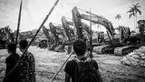 Eine Gruppe junger Männer der Kichua überwacht Maschinen, die von einer Baufirma zurückgelassen wurden. Hier soll ein Wasserkraftwerk entstehen.