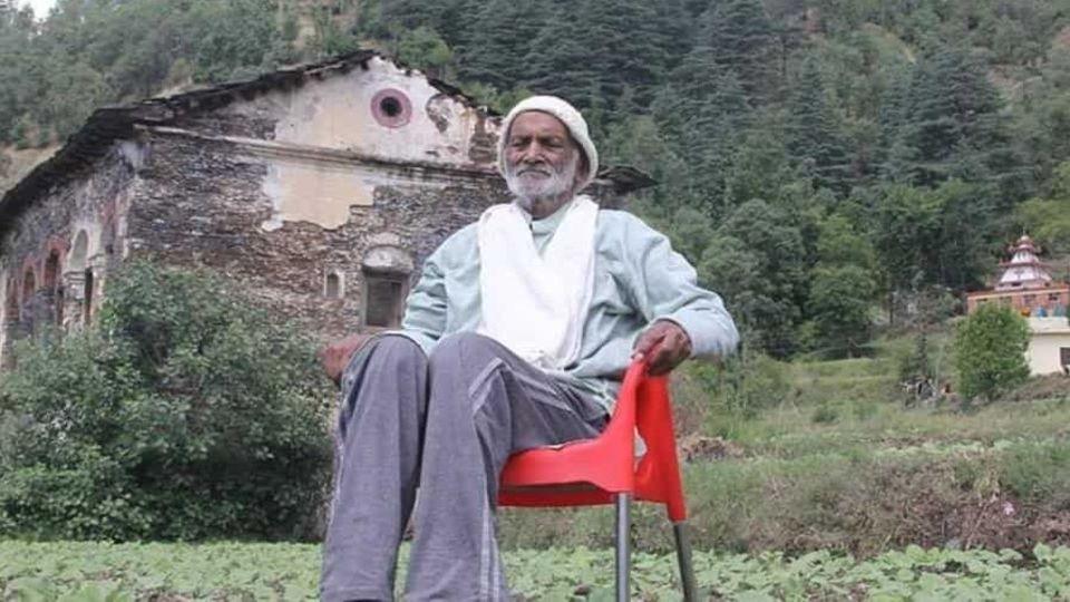 Vishweshwar Dutt Saklani sitzt mit geschlossenen Augen im Grünen auf einem Stuhl