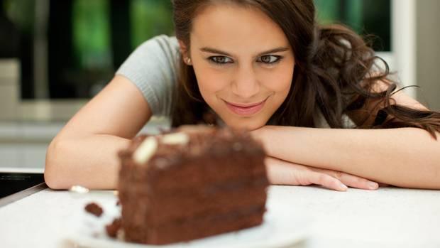 Eine Frau schaut lächelnd ein Stück Schokoladentorte an