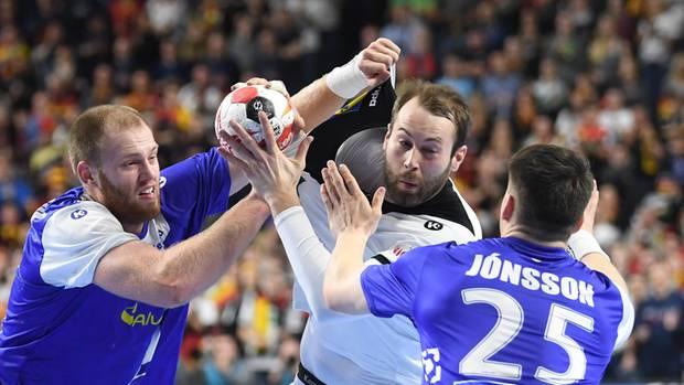 Ein deutscher Handball-Spieler versucht mit dem Ball zwischen zwei isländischen Gegenspielern durchzukommen