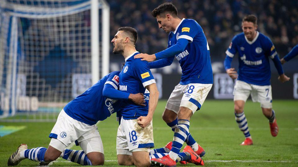 Drei Schalker Spieler knien neben dem Tor und jubeln über einen Treffer