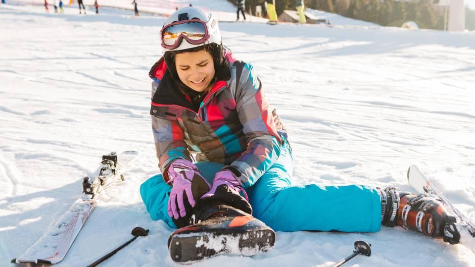Eine junge Frau sitzt mit schmerzverzerrtem Gesicht auf einer Skipiste