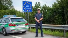 Ein bayerischer Grenzpolizist steht hinter einem BMW-Komb iauf dem Standstreifen