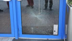 Das Glas einer Eingangstür mit blauem Metallrahmen ist gesprungen