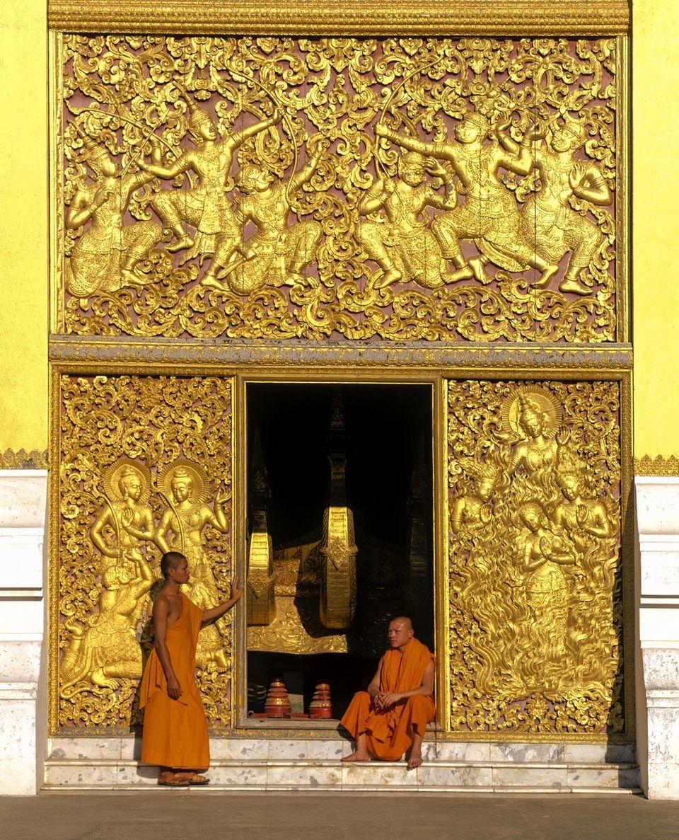 Mönche und goldene Reliefsam Eingang zum Carriage House, des TempelsWat Xiengtong
