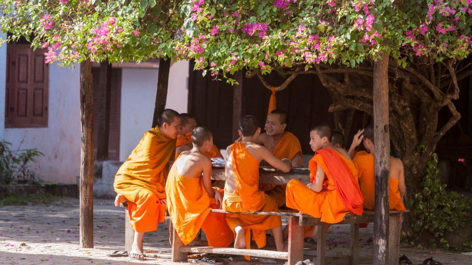 Zwischen Gebet, Arbeit und Meditation treffen sich Mönche im Hof des Wat Si Bun Heuang zu einem Plausch.