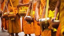 Tagtägliche buddhistische Praxis: der frühmorgendliche Bettelgang Tak Bat. In den Henkeltöpfen sammeln Mönche Spenden von Gläubigen.
