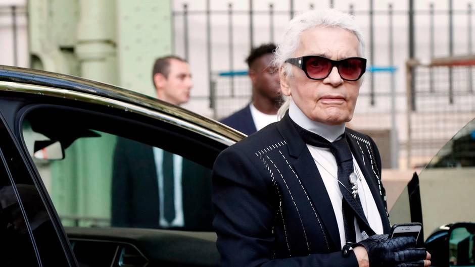 Karl Lagerfeld steigt im typischen Look mit Sonnenbrille und Handschuhen aus einer Limousine aus