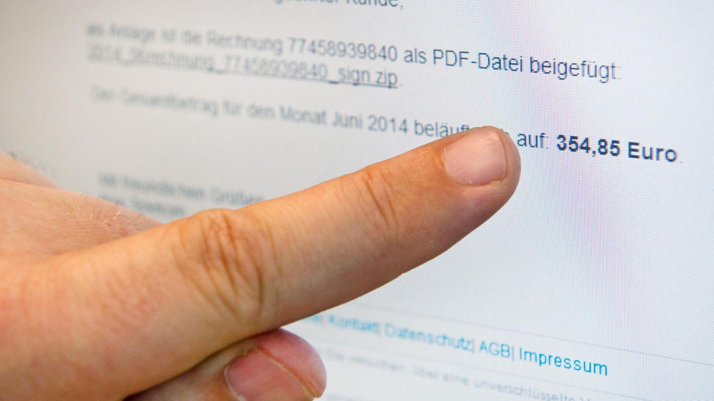 Ein Mann zeigt auf einen Monitor, auf dem eine gefälschte E-Mail der Telekom Deutschland GmbH angezeigt wird.