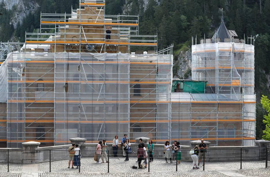 Während der Renovierungsphase nicht besonders fotogen:Touristen stehen vor dem eingerüsteten Torhaus von Schloss Neuschwanstein.