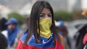 Eine Frau hat sich mit einer venezolanischen Flagge maskiert