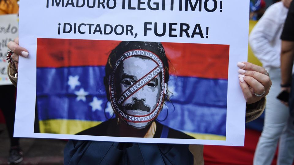 """""""Maduro, illegitimer Diktator, verschwinde"""", steht auf einem Plakat eines Demonstranten"""