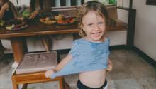 Ein kleines Mädchen mit vollgekleckertem T-Shirt lacht in die Kamera