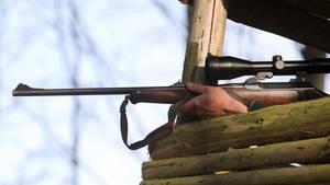 Ein Jäger hält sein Gewehr in einem Hochsitz